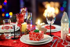 Beautiful table setting for Christmas party or New Year celebration at home. Cozy room with a fireplace and Christmas tree in a ba. Ckground. Xmas time with stock photo
