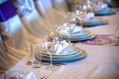 Beautiful table setting with crockery and flowers for a party, wedding reception or other festive event. Glassware and cutlery for catered event dinner Royalty Free Stock Photo