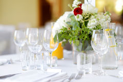 Beautiful table setting with crockery and flowers for a party, wedding reception or other festive event. Glassware and cutlery for catered event dinner stock photos