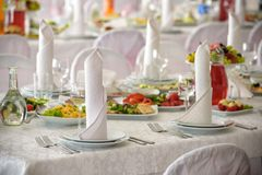 Beautiful table setting with crockery and flowers for a party, wedding reception or other festive event. Glassware and cutlery for. Catered event dinner Stock Photography