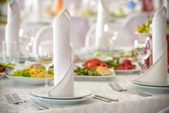 Beautiful table setting with crockery and flowers for a party, wedding reception or other festive event. Glassware and cutlery for. Catered event dinner Stock Image