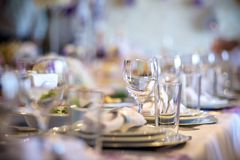 Beautiful table setting with crockery and flowers for a party, wedding reception or other festive event. Glassware and cutlery for catered event dinner Royalty Free Stock Image