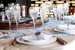 Beautiful table setting with crystal glasses. Beautiful table setting with golden cutlery and crystal glasses Stock Images