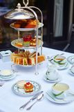 Beautiful table setting for high tea ceremony. Beautiful table setting with selection of sandwiches, fancy cakes, tea and champagne served for the ceremony of Stock Image