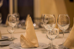 Beautiful table setting. Serving of glasses and napkins on the table royalty free stock images