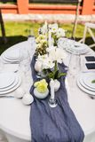 Beautiful table setting with white and green flowers. Different types of bottles, glasses and plates Stock Photos