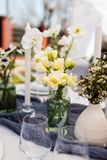 Beautiful table setting with white and green flowers. Different types of bottles, greenery trend Royalty Free Stock Image