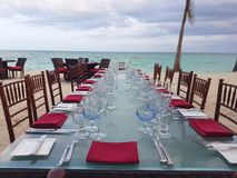 Beautiful table setting in white and red next to the beach in Bahamas. Blue crystal wine glass and red napkins. Beautiful table setting in white and red next to royalty free stock photos