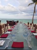 Beautiful table setting in white and red next to the beach in Bahamas. Blue crystal wine glass and red napkins stock photography