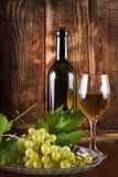 Table white wine in glass and black bottle on desk with grape stock photos