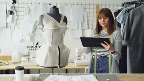 Beautiful tailor is turning tailoring dummy to check pinned clothing and working with tablet to enter information. Using. Beautiful female tailor is turning stock footage