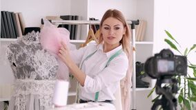 Beautiful tailor woman is filming a tutorial how to sew a delicate dress