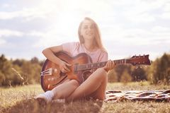 Beautiful talented young female musician plays acoustic guitar, has gentle smile on face, sits on green grass of meadow, has joyfu. L expression, sings her Stock Photography