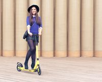 Beautiful tall brunette girl posing on yellow scooter Royalty Free Stock Photo