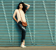 Beautiful tall brunette girl stands near a wall of colored wooden planks Royalty Free Stock Photography
