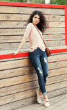 Beautiful tall brunette girl stands near a wall wooden planks Stock Photo