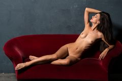 Brunette on a red sofa Stock Photos