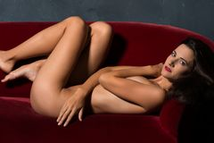 Brunette on a red sofa Stock Photography