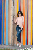 Beautiful tall girl with long hair brunette in glasses standing near colorful wall background Royalty Free Stock Image