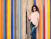 Beautiful tall girl with long hair brunette in glasses standing near colorful wall background Royalty Free Stock Images