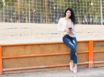 Beautiful tall girl with long hair brunette in jeans sits near a sports court with a cup of coffee on a warm summer evening Royalty Free Stock Images