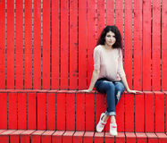 Beautiful tall girl with long hair brunette in jeans sits near wall of red wooden planks Royalty Free Stock Photo