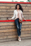 Beautiful tall girl with long hair brunette in jeans standing on old wooden planks with a cup of coffee in hand  on a warm summer Royalty Free Stock Photo