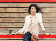 Beautiful tall girl with long hair brunette in jeans standing on old wooden planks with a cup of coffee in hand  on a warm summer Royalty Free Stock Images