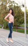 Beautiful tall girl with long hair brunette in jeans standing on old wooden planks on a warm summer evening Stock Photos