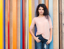 Beautiful tall girl with long hair brunette standing near colorful wall background Royalty Free Stock Photography