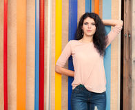 Beautiful tall girl with long hair brunette standing near colorful wall background Royalty Free Stock Photo