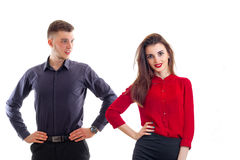 Beautiful tall guy keeps his hands on the sides and looks at an attractive girl in the red shirt. Isolated on white background Stock Photos