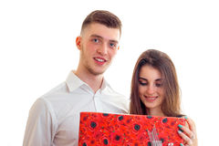 Beautiful tall guy in a shirt with a cute girl and she looks a gift  on a white background. Close-up Royalty Free Stock Images