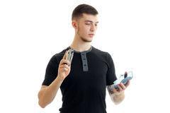 Beautiful tall guy in a t-shirt holding a shaving Clipper. Is isolated on a white background Royalty Free Stock Photos