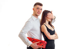 Beautiful tall smiling guy in the white shirt brought girl gift and closed her eyes hand. Isolated on white background Royalty Free Stock Photography