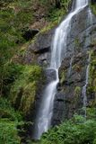 Beautiful tall waterfall flowing over lush green landscape folia. Stunning tall waterfall flowing over lush green landscape foliage in early Autumn stock photography