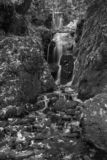 Beautiful tall waterfall flowing over lush green landscape folia. Stunning tall waterfall in landscape foliage in early Autumn in black and white royalty free stock photography