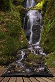 Beautiful tall waterfall flowing over lush green landscape foliage in early Autumn coming out of pages of open story book. Stunning tall waterfall flowing over stock images