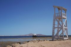 Beautiful tall white watch tower on the seashore nature background stock photos