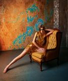 Beautiful tall young blond woman with artistic golden makeup. Posing in the luxurious studio stock image