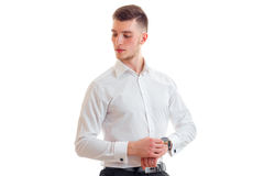 Beautiful tall young guy in a white shirt corrects watches on hand. On white background Royalty Free Stock Images