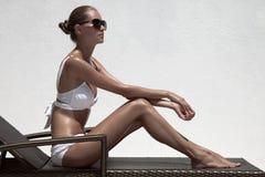 Beautiful tan female model sunbathing in bikini on chaise-longue Stock Photos