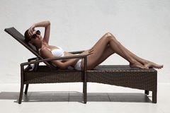 Beautiful tan female model sunbathing in bikini on chaise-longue Royalty Free Stock Photography