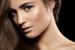 Beautiful tan model face, shiny clean skin, volume hair. Fashionable close-up portrait of glamour woman model with evening make-up, beautiful long volume shiny Stock Images