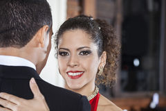 Beautiful Tango Dancer Performing Gentle Embrace Step With Man. Portrait of beautiful female tango dancer performing gentle embrace step with men in restaurant Royalty Free Stock Photos