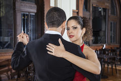 Beautiful Tango Dancer Performing Gentle Embrace Step With Partn. Portrait of beautiful female tango dancer performing gentle embrace step with partner in Stock Photos