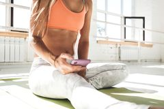 Fit female athlet warming up before workout and hold smartphone in hand early morning in sunny gym. Beautiful tannde woman looks at smartphone and counts up stock images