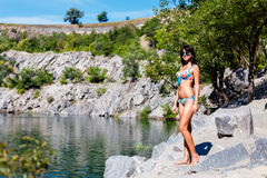 Beautiful tanned brunette girl in a colorful bikini standing on Stock Images