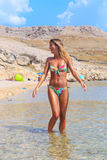 Beautiful tanned girl in a bikini standing in a water Royalty Free Stock Image