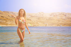 Beautiful tanned girl in a bikini standing in a water and waiving Stock Photography